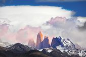 Three rock Torres del Paine lit pink rays of sunset. Patagonia