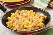 stock photo of scrambled eggs  - Scrambled eggs with diced ham and cheese in a frying pan - JPG