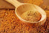 Mustard powder in wooden spoon on mustard seeds, on  wooden background