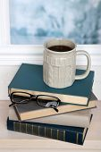 Composition of books, cup and glasses on the windowsill on light background
