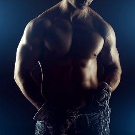 stock photo of macho man  - Sexy macho man with chain and gloves in dark - JPG