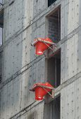 foto of chute  - 2 orange rubbish chute heads attached to the side of building under construction - JPG
