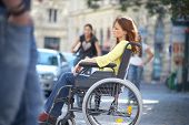foto of rollator  - lonely girl is sitting on a wheelchair on the street - JPG