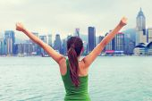 pic of cheer-up  - Happy woman success cheering by Hong Kong skyline with arms raised up outstretched - JPG