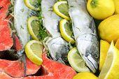 stock photo of redfish  - Dish With Fresh Stuffed Fish Salmon Steaks Lemon Slice And Herbs Close - JPG