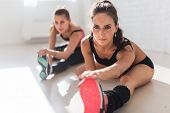 picture of strength  - Group of fit women working stretching leg muscles and back to warm up at gym fitness, sport, training and lifestyle concept