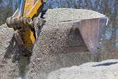 picture of excavator  - Close up of excavator bucket scooping gravel from pile for road construction - JPG