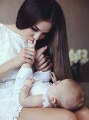 stock photo of young baby  - tender photo of beautiful young mother with long dark hair posing with her little adorable baby mom kissing baby feets - JPG