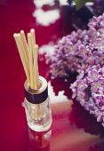 stock photo of diffusion  - Aroma diffuser with bamboo sticks mounted and branches of lilac on red - JPG