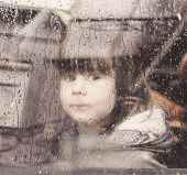 image of child missing  - child looking through the car window on a rainy day - JPG
