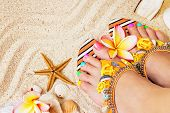 foto of pedicure  - Female feet with pretty multicolor pedicure on sand with frangipani flowers and seashells - JPG