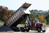 image of dump_truck  - peterbilt dump truck dumping dirt at construction site - JPG