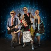 stock photo of rockabilly  - Rockabilly family band having fun playing music and posing with vintage microphone  - JPG