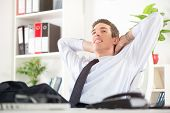 image of daydreaming  - Young successful businessman relaxing in the office with hands behind head and daydreaming - JPG