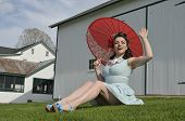 picture of farmhouse  - pretty pin up girl sitting on the grass in front of an old farmhouse - JPG