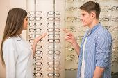 stock photo of optical  - Optical store client man and professional specialist help to choose - JPG
