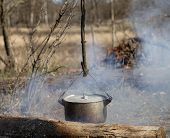 foto of smut  - Cooking in sooty cauldron on campfire at spring forest - JPG