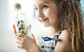 foto of passenger ship  - Little girl holding ship in a bottle - JPG