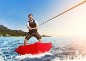 stock photo of ski boat  - Businessman on water skis in umbrella - JPG