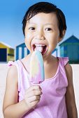 image of licking  - Portrait of cheerful little girl standing on the beach while wearing swimwear and licking ice cream - JPG