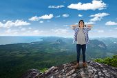 stock photo of cliffs  - Portrait of young man standing on the cliff edge at the mountain while relaxing and enjoy the fresh air - JPG