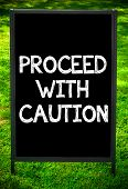 stock photo of proceed  - PROCEED WITH CAUTION message on sidewalk blackboard sign against green grass background - JPG