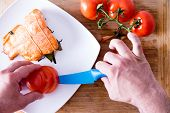 pic of plate fish food  - Chef plating up a gourmet salmon dinner carefully arranging sliced fresh tomato alongside an oven - JPG