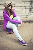 picture of snickers  - Blond teenage girl in jeans and sunglasses sits on her skateboard near urban brick wall vertical photo with warm retro tonal correction effect instagram old style filter - JPG