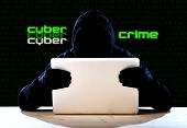 stock photo of hack  - hacker man in black hood and mask with computer laptop in dangerous dark look hacking system having access to data info and privacy in business digital intruder and cyber crime concept - JPG