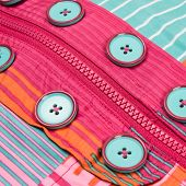 stock photo of zipper  - Close up zipper and button on a colorful background - JPG