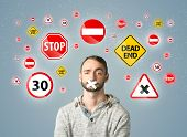 foto of taboo  - Young man with taped mouth and traffic signals around his head   - JPG