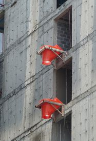 stock photo of chute  - 2 orange rubbish chute heads attached to the side of building under construction - JPG