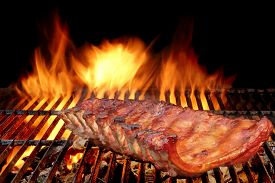 picture of charcoal  - BBQ Baby Back Spicy Marinated And Smoked Pork Ribs On The Hot Charcoal Grill With Bright Flames On Black Background - JPG
