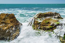 picture of slam  - Turquoise rolling wave slamming on the rocks of the coastline - JPG