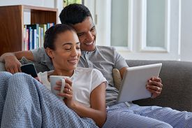 pic of pyjama  - smiling couple with tablet computer on sofa couch at home - JPG