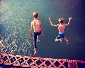 stock photo of trestle bridge  -  two boys jumping of an old train trestle bridge into a river toned with a retro vintage instagram filter effect app or action - JPG