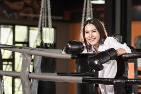 stock photo of boxing  - Businesswoman boxer in suit and boxing gloves on boxing ring smiling happy - JPG