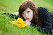 Sad Young Woman Lying On The Grass