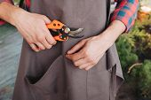 Partial View Of Gardener In Apron Holding Pruning Shears In Hand poster