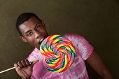 Young Man Bites Into A Giant Lollipop