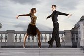 Pair of dancers dancing ballroom on sky background poster