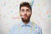 Portrait Of Bearded Man Who Is Celebrating His Birthday Party, Wearing Light Blue Shirt And Party Ca poster