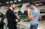 Handsome young car salesman showing a new car to the customer at the dealership poster