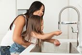 Young asian mother helping her daughter to wash hands in a sink on a kitchen poster
