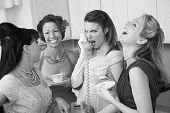 image of foursome  - Outraged woman on phone with three friends in a kitchen - JPG