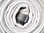 stock photo of firehose  - A white firehose coiled and ready to go in case of an emergency - JPG
