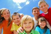 stock photo of family fun  - A family has fun outdoors crowding together and smiling into the camera - JPG