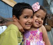 stock photo of east-indian  - Young brother and sister hugging affectionately and smiling happily - JPG