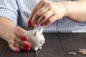 Savings Concept,white Piggy Bank With Human Female Hand Inserting  Coin Inside poster