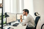 Busy Working. Handsome Bearded Trader In Formal Wear And Eyeglasses Is Analyzing Trading Charts And  poster